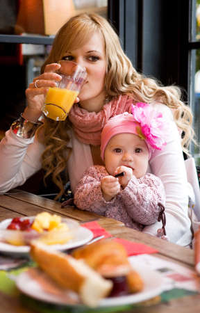 Young mother and baby daughter having breakfast together in a Parisian cafe