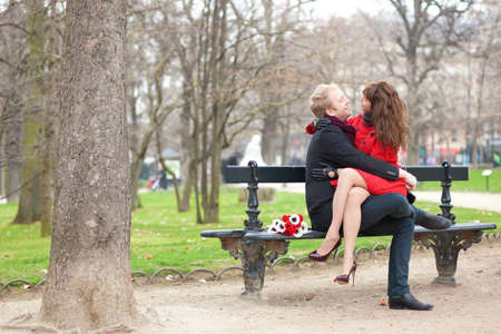 Happy romantic couple hugging on a bench