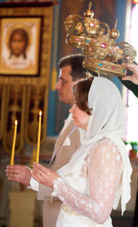Bride and groom during orthodox wedding ceremony with candles and crowns