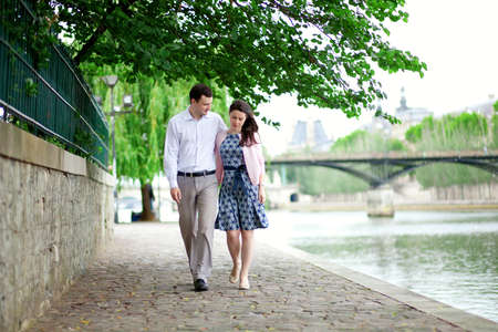 Romantic dating couple is walking by the water in Paris