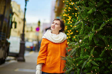 Cheerful young woman in Paris on a winter day, enjoying Christmas season