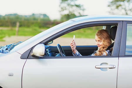 Young woman using her smartphone and making selfie while driving a car