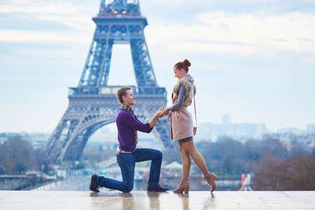 Photo pour Romantic engagement in Paris, man proposing to his beautiful girlfriend near the Eiffel tower - image libre de droit