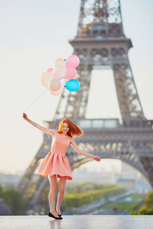 Foto de Happy young girl with bunch of pink and blue balloons in front of the Eiffel tower in Paris, France - Imagen libre de derechos