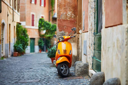 Photo for Old fashioned orange motorbike on a street of Trastevere district, Rome - Royalty Free Image