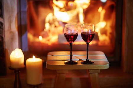 Foto de Two glasses of red wine near fireplace with many candles. Cozy romantic evening for couple or Christmas celebration concept - Imagen libre de derechos