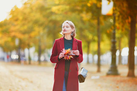 Foto de Beautiful young woman with bunch of colorful autumn leaves walking in park on a fall day - Imagen libre de derechos