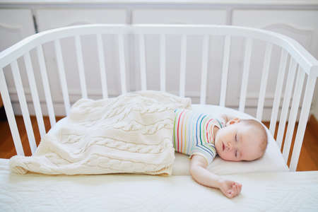 Foto de Adorable baby girl sleeping in co-sleeper crib attached to parents' bed. Little child having a day nap in cot. Infant kid in sunny nursery - Imagen libre de derechos