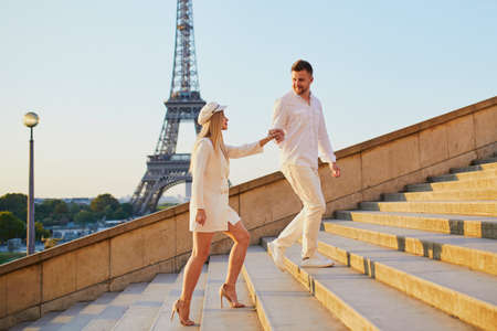 Foto de Happy couple near the Eiffel tower. Tourists enjoying their vacation in France. Romantic date or traveling couple concept - Imagen libre de derechos