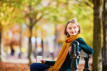 Photo pour Happy young girl in yellow scarf with coffee to go walking in autumn park on a bright fall day - image libre de droit