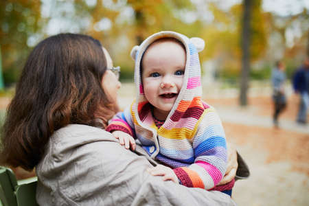 Photo pour Happy middle aged woman with baby girl on sunny fall day in park. Grandmother having fun with granddaughter outdoors. Autumn activities with kids - image libre de droit