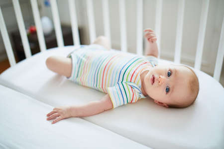 Foto de Adorable baby girl in co-sleeper crib attached to parents' bed. Little child having a day nap in cot. Infant kid in sunny nursery - Imagen libre de derechos