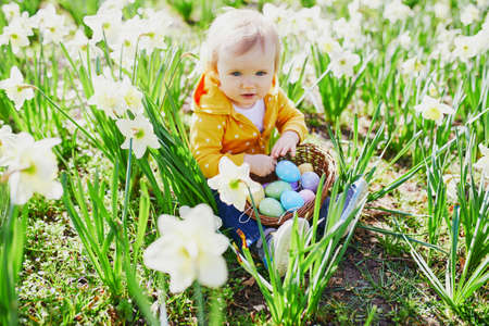 Photo for Cute little one year old girl playing egg hunt on Easter. Toddler sitting on the grass with many narcissi and gathering colorful eggs in basket. Little kid celebrating Easter outdoors in park or forest - Royalty Free Image