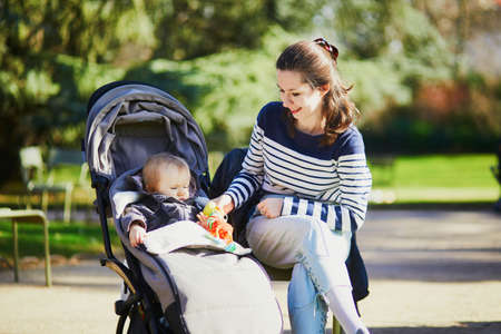 Photo pour Young woman with toddler girl in pushchair walking together in Luxembourg garden of Paris, France. Mother and daughter in park on a sunny day. Student babysitter taking care of little kid - image libre de droit