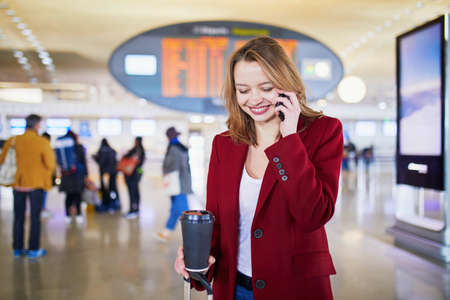 Young woman in international airport with luggage and coffee to go, speaking on the phone and waiting for her flight