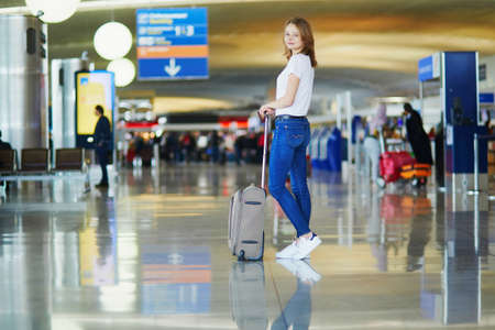 Photo pour Young woman in international airport walking with luggage, ready for her flight - image libre de droit