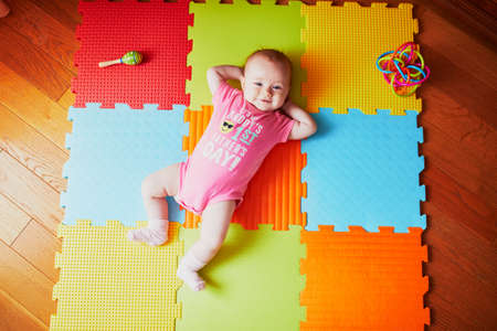 Foto de 4 months old baby girl lying on colorful play mat on the floor in bodysuit with words 'It's my daddy's first father's day'. Activity carpet for kids - Imagen libre de derechos