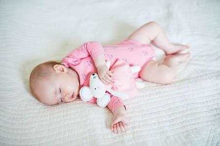 Foto de Baby girl having a nap with her favorite mouse toy. Little child sleeping on bed with comforter. Sleep training concept. Infant kid in sunny nursery - Imagen libre de derechos