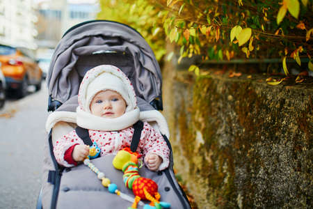 Foto de Happy little child, baby girl in stroller with colorful autumn leaves outdoors on a sunny fall day. Outdoors seasonal activities for kids - Imagen libre de derechos