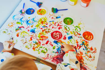 Foto de Hand of little girls painting with fingers at home, in kindergaten or preschool. Creative games for kids - Imagen libre de derechos