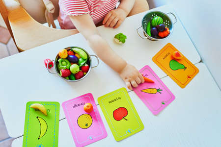 Photo pour Little girl playing with toy fruits and vegetables at home, in kindergaten or preschool; trying to match figurine with image on a card. Words on cards written in French. Indoor creative games for kids - image libre de droit