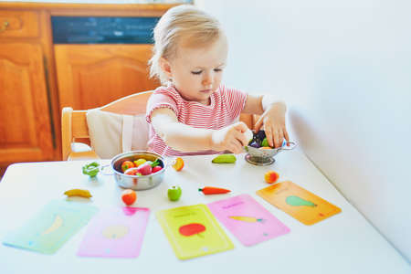 Photo pour Adorable little girl playing with toy fruits and vegetables at home, in kindergaten or preschool; trying to match figurine with image on a card. Words on cards written in French. Indoor creative games for kids - image libre de droit