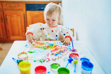 Photo pour Adorable little girl painting with fingers at home, in kindergaten or preschool. Indoor creative games for kids - image libre de droit
