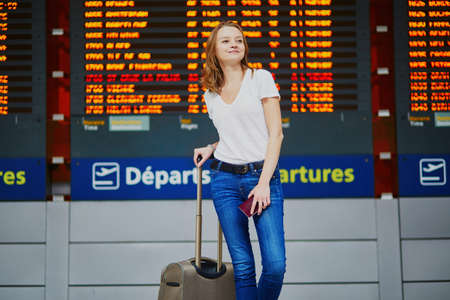 Photo pour Young woman in international airport with luggage and passport near flight information display - image libre de droit