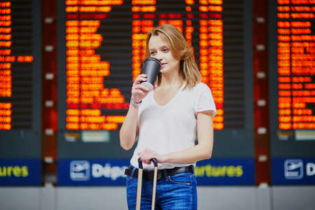 Photo pour Young woman in international airport with luggage and coffee to go near flight information display - image libre de droit