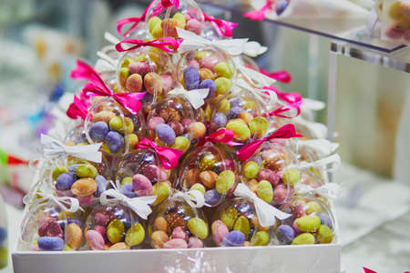 Photo pour Colorful candies in transparent bags at wedding reception or event party. Individual presents for guests - image libre de droit