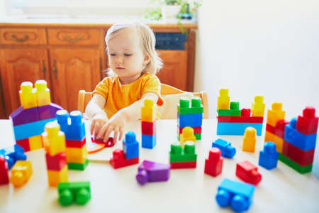 Photo pour Adorable little girl playing with colorful plastic construction blocks at home, in kindergaten or preschool. Creative games for kids - image libre de droit