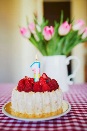 Photo pour Delicious fruit cake with raspberries and candle in form of number one with bunch of beautiful pink tulipes in vase. Baby's very first birthday concept - image libre de droit