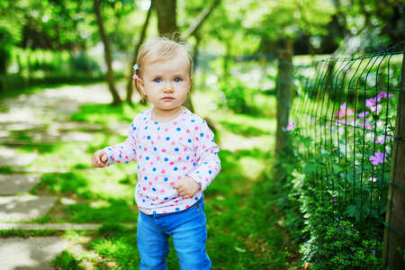 Photo for Adorable toddler girl walking in green park on a summer day. Little child having fun outdoors. Kid exploring nature - Royalty Free Image