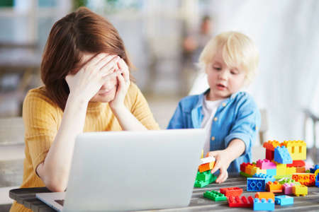 Photo for Boy playing near his tired mother working on her laptop. Quarantine and closed schools and offices during coronavirus outbreak. Homeschooling, distance learning and freelance job - Royalty Free Image