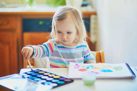 Photo pour Adorable little girl painting with aquarelle at home, in kindergaten or preschool. Creative games for kids staying at home - image libre de droit