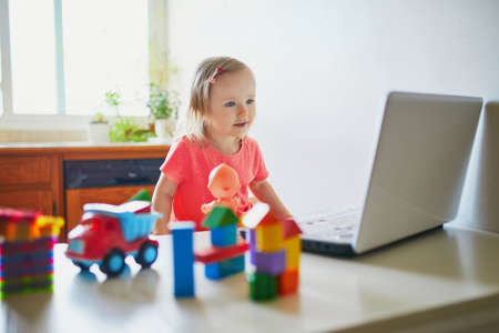 Photo pour Happy toddler girl with laptop and toys. Kid using computer to communicate with friends, elderly relatives or kindergartners. Education or online communication for kids. Stay at home entertainment - image libre de droit
