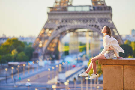 Photo pour Beautiful young girl sitting near the Eiffel tower in Paris. Tourist enjoying her vacation in France - image libre de droit