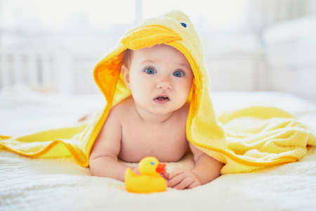 Photo for Cute little girl playing with rubber duck after having bath. Happy kid in yellow towel - Royalty Free Image