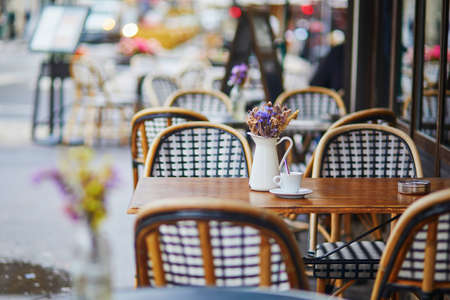 Photo pour Table of traditional Parisian outdoor cafe. Cup of coffee and pitcher with dried flowers in empty restaurant in Paris, France - image libre de droit