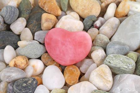 Beautiful roze quartz gem heart on pebbles