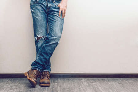 Photo for Young fashion man's legs in jeans and boots on wooden floor - Royalty Free Image
