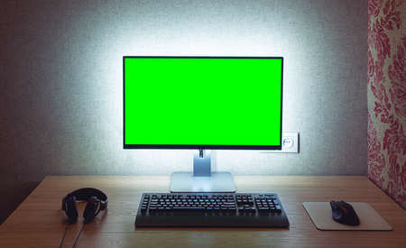 Photo pour Blank chromakey monitor with keyboard and mouse with backlight over gray wall in dark room - image libre de droit