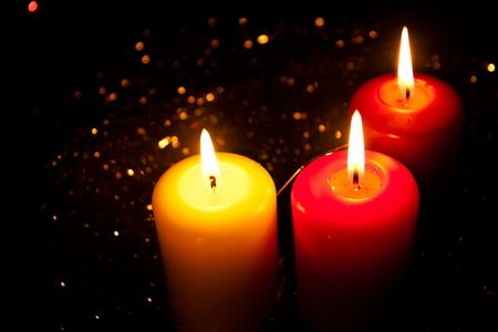 Three burning candles stand in a tinsel