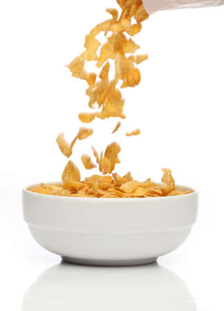 Pouring cornflakes into a bowl, over white background
