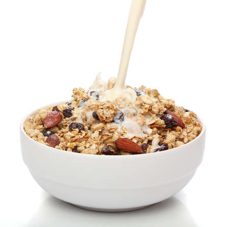 Pouring milk into a bowl with granola cereal