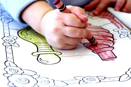 Little child colring in coloring book with crayons