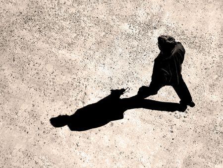 Man walking on sidewalk with black shadow