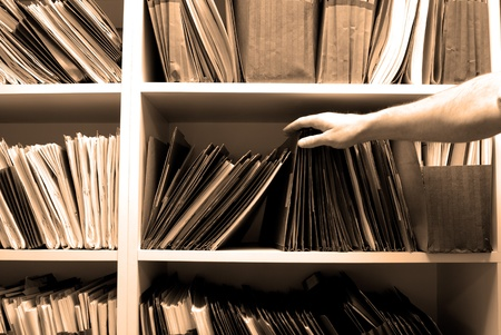 Man reaching for files on shelf in a file room