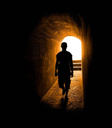 Person in long tunnel walkway with white light at the end