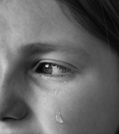 Portrait of girl crying with tears rolling down her cheeks